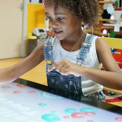 Young girl plays on interactive gaming table