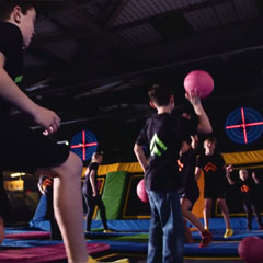 Kids play dodgeball in trampoline park with Rugged Interactive DodgeAttack