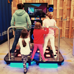 Females playing StepManiaX interactive dance & step game