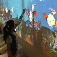 Female uses aquarium-themed TouchMagix interactive touch wall