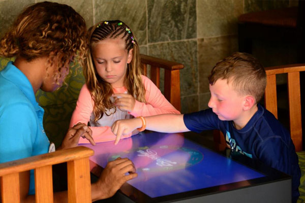 Adult and kids playing interactive games on touch-table