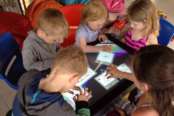Group of children using After-Mouse.com interactive play table