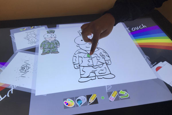 Child using interactive touch-table colouring program