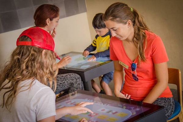 Children and adults play together with interactive touch tables