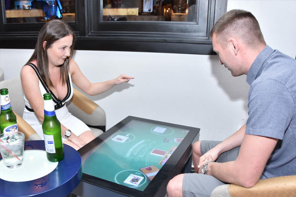 Woman and man playing games on interactive play tables