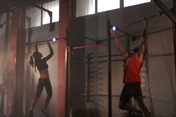 Woman and man compete using BlazePod fitness tech touch sensors on exercise bars