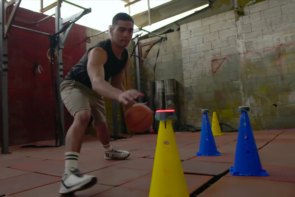 Man fitness training with basketball and BlazePod touch sensors