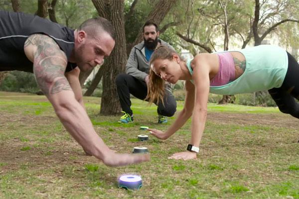 Man and woman training outdoors with fitness tech BlazePod wireless touch sensors