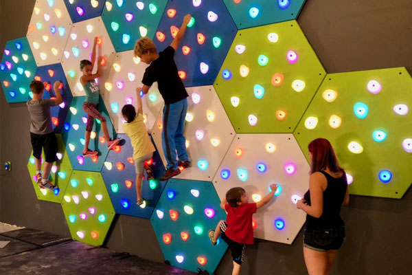 Kids playing on GlowHolds illuminated climbing wall system