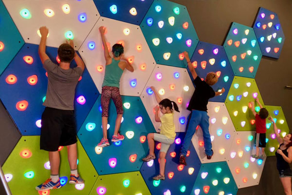 Kids play on GlowHolds interactive climbing wall