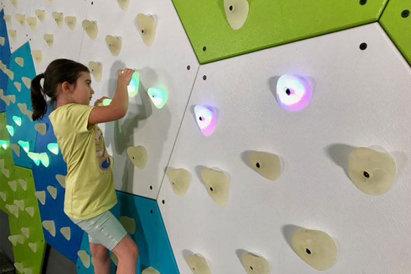 Young girl climbing GlowHolds wall with safety matting