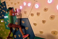 Young girl on climbing wall with GlowHolds