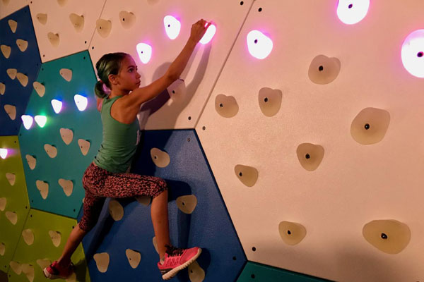 Young girl active with GlowHolds climbing wall system