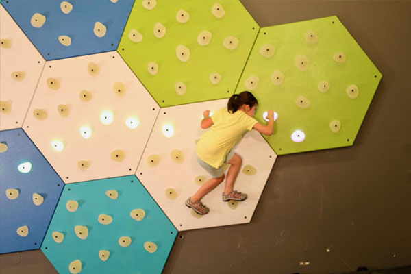 Young girl active with GlowHolds illuminated climbing wall