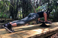 Young woman doing plank exercise with Stealth Personal Trainer